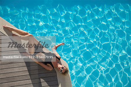 Elevated view of a woman sunbathing on the edge of a swimming pool Stock Photo - Rights-Managed, Image code: 822-03407095