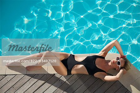 Elevated view of a woman sunbathing on the edge of a swimming pool Stock Photo - Rights-Managed, Image code: 822-03407120