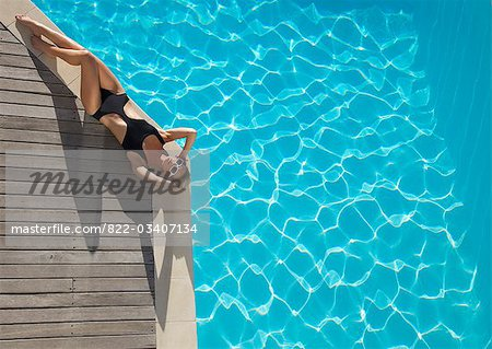 Elevated view of a woman sunbathing on the edge of a swimming pool Stock Photo - Rights-Managed, Image code: 822-03407134