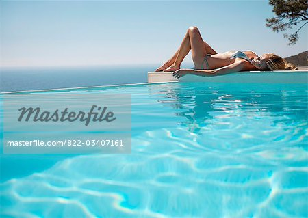 Woman sunbathing by a swimming pool with ocean in the background Stock Photo - Rights-Managed, Image code: 822-03407161