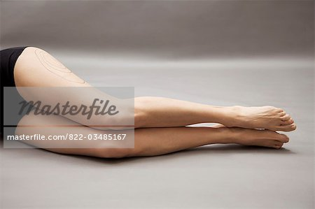 Woman lying on side with liposuction markings on her thigh, headless Stock Photo - Rights-Managed, Image code: 822-03485167
