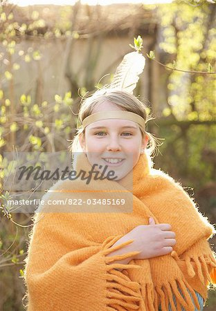 Girl wrapped in a blanket wearing Indian feather headdress Stock Photo - Rights-Managed, Image code: 822-03485169