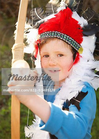 Boy wearing Indian chief feather headdress holding bow and arrow