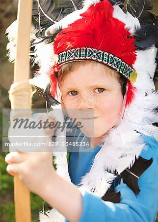 Boy wearing Indian chief feather headdress holding bow and arrow Stock Photo - Rights-Managed, Image code: 822-03485234