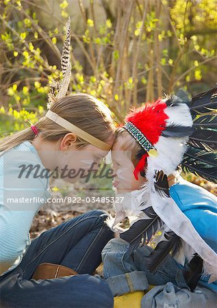 Boy and girl wearing Indian feather headdresses sitting face to face Stock Photo - Rights-Managed, Image code: 822-03485327