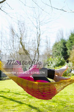 Profile of a girl lying on a hammock hugging her knees