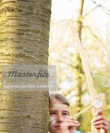 Girl hiding behind tree wearing Indian feather headdress holding bow and arrow, close up Stock Photo - Rights-Managed, Image code: 822-03485437