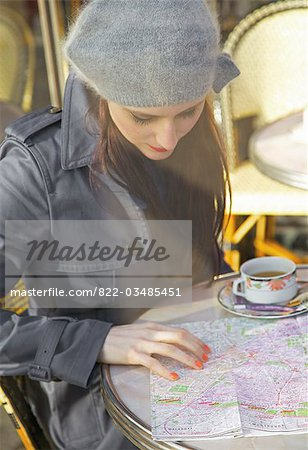 Young woman at cafe looking over a map Stock Photo - Rights-Managed, Image code: 822-03485451