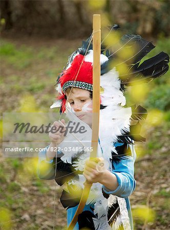 Boy wearing Indian chief feather headdress holding bow and arrow Stock Photo - Rights-Managed, Image code: 822-03485465