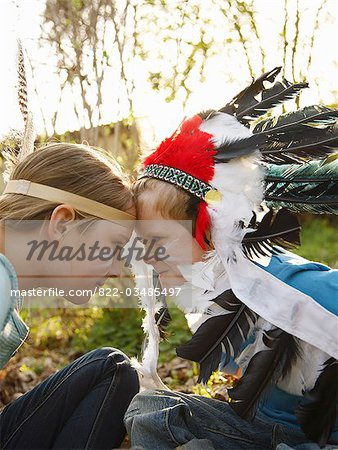 Boy and girl wearing Indian feather headdresses sitting face to face Stock Photo - Rights-Managed, Image code: 822-03485497