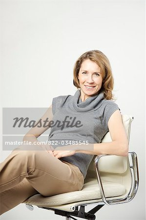Portrait of a woman sitting on chair Stock Photo - Rights-Managed, Image code: 822-03485545