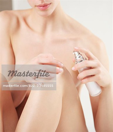 Close up of a nude woman applying cosmetic cream on her knee Stock Photo - Rights-Managed, Image code: 822-03485555