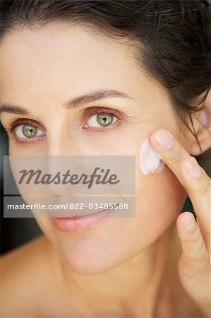 Close up of a woman applying cosmetic cream Stock Photo - Rights-Managed, Image code: 822-03485588