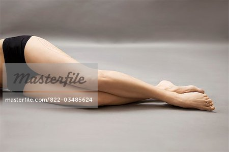 Woman lying on side with liposuction markings on her thigh, headless Stock Photo - Rights-Managed, Image code: 822-03485624