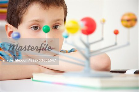 Boy Inspecting Solar System Model Stock Photo - Rights-Managed, Image code: 822-03601647