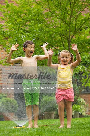 Boy and Girl Playing with Sprinkler Stock Photo - Rights-Managed, Image code: 822-03601674