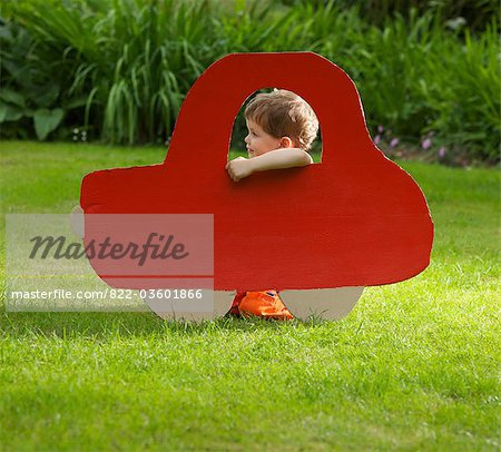 Young Boy Kneeling behind Cardboard Cut Out in Shape of Car Stock Photo - Rights-Managed, Image code: 822-03601866
