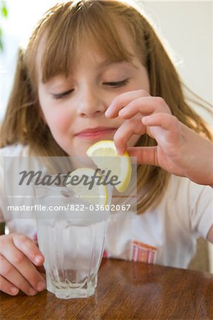 Girl Playing with Slice of Lemon over a Glass of Water Stock Photo - Rights-Managed, Image code: 822-03602067