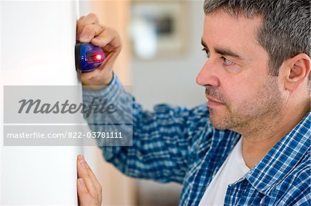 Profile of Man Holding Laser Level against White Wall Stock Photo - Rights-Managed, Image code: 822-03781111