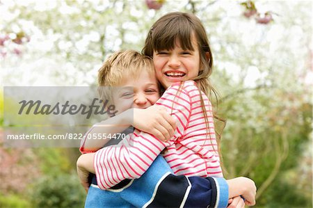 Smiling Boy and Girl Hugging Outdoors Stock Photo - Rights-Managed, Image code: 822-05554470