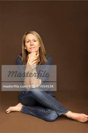 Woman Sitting Cross Legged Leaning on Elbows Stock Photo - Rights-Managed, Image code: 822-05554534