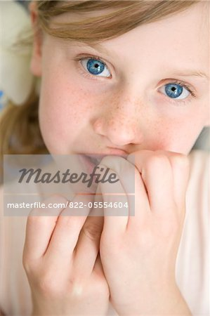 Young Girl with Fingers in Front of Mouth Stock Photo - Rights-Managed, Image code: 822-05554604