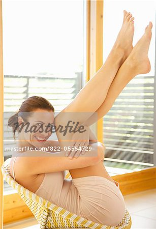 Smiling Woman Sitting on Chair with Arms Around Legs Stock Photo - Rights-Managed, Image code: 822-05554729