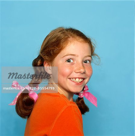 Smiling Girl Looking Over Shoulder Stock Photo - Rights-Managed, Image code: 822-05554799