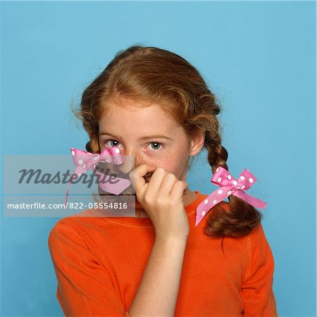 Girl Covering Mouth with Braid Stock Photo - Rights-Managed, Image code: 822-05554816
