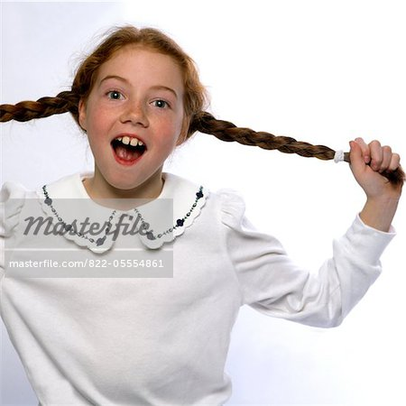 Smiling Girl with Mouth Open Pulling her Braids Stock Photo - Rights-Managed, Image code: 822-05554861