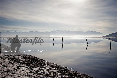 Man Crouching on Lakeshore Admiring Mountain View Stock Photo - Rights-Managed, Image code: 822-05554983