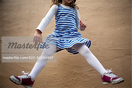 Girl Jumping Mid Air in front of Wall, Cropped Stock Photo - Rights-Managed, Image code: 822-05554997