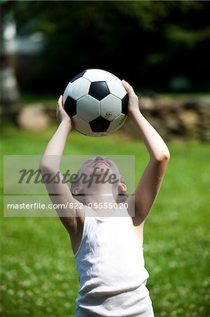 Smiling Young Girl Holding Football Above Head Stock Photo - Rights-Managed, Image code: 822-05555020