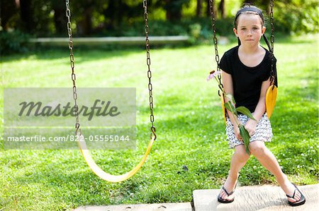 Girl Sitting on Swing Holding Flower Stock Photo - Rights-Managed, Image code: 822-05555044