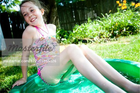 Girl Leaning on the Edge of Paddling Pool Stock Photo - Rights-Managed, Image code: 822-05555126