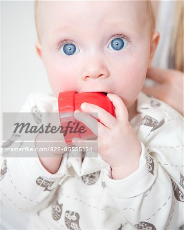 Wide Eyed Baby Biting Toy, Close-up view Stock Photo - Rights-Managed, Image code: 822-05555154