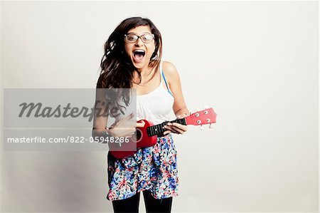 Laughing Woman Playing Small Guitar Stock Photo - Rights-Managed, Image code: 822-05948286