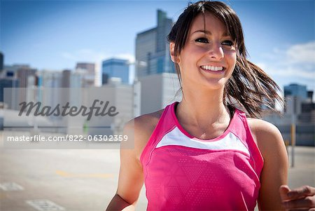 Smiling Young Woman Running Outdoors Stock Photo - Rights-Managed, Image code: 822-06302359