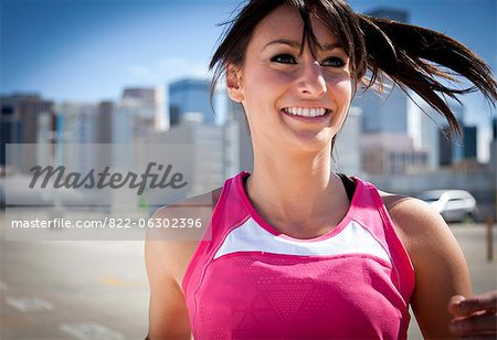 Smiling Young Woman Running Outdoors Stock Photo - Rights-Managed, Image code: 822-06302396