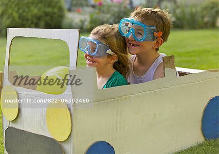 Boy and Girl Wearing Goggles Driving Cardboard Car Stock Photo - Rights-Managed, Image code: 822-06302460