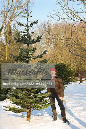 Man Holding Christmas Tree and Handsaw Stock Photo - Rights-Managed, Image code: 822-06302475