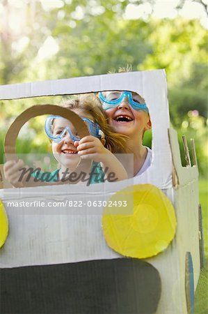 Boy and Girl Wearing Goggles Driving Cardboard Car Stock Photo - Rights-Managed, Image code: 822-06302493