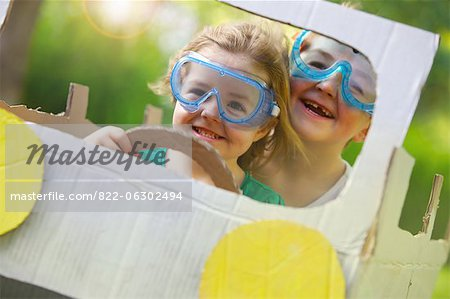 Boy and Girl Wearing Goggles Driving Cardboard Car Stock Photo - Rights-Managed, Image code: 822-06302494