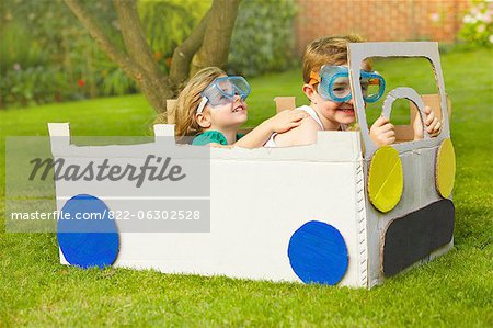 Boy and Girl Wearing Goggles Driving Cardboard Car Stock Photo - Rights-Managed, Image code: 822-06302528