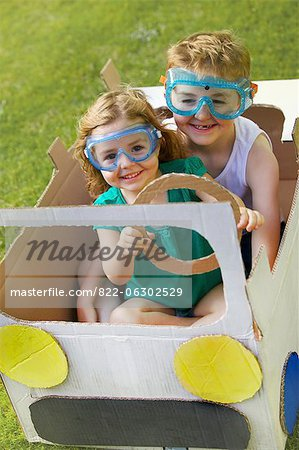 Boy and Girl Wearing Goggles Driving Cardboard Car Stock Photo - Rights-Managed, Image code: 822-06302529