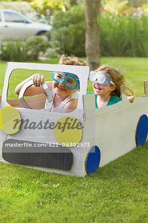 Boy and Girl Wearing Goggles Driving Cardboard Car Stock Photo - Rights-Managed, Image code: 822-06302573