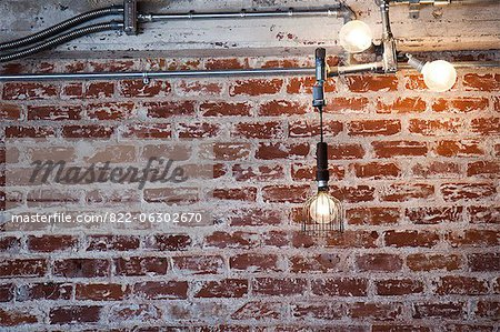 Illuminated Light Bulbs Hanging in front of Brick Wall  Stock