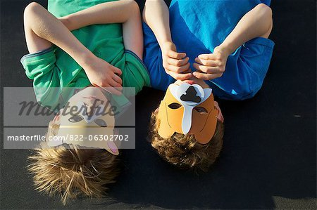 Two Boys Wearing Animal Masks lying on Back Stock Photo - Rights-Managed, Image code: 822-06302702
