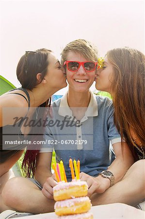 Two Teenage Girls Kissing Teen Boy in front of Birthday Cake Stock Photo - Rights-Managed, Image code: 822-06702179