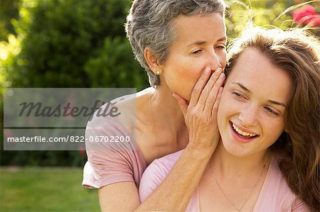 Mother Whispering into Daughter's Ear Stock Photo - Rights-Managed, Image code: 822-06702200